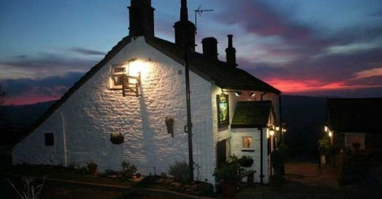 Picture of the exterior of the cosy Hanging Gate pub at night