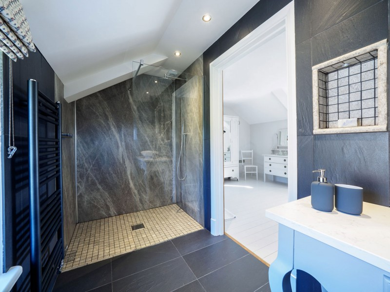 Picture of en-suite wet room with large radiator and slate floor and walls